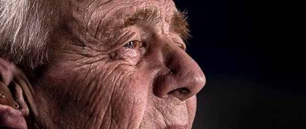 Elderly man side profile with his hearing aid